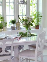 Rhubarb and lilac on dining table with white chairs