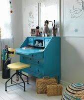 Vintage swivel chair at blue bureau below white-framed drawings on wall