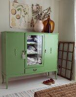 Vases of flowering branches on top of half-height, green linen cupboard