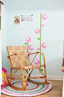 Rocking chair with woven textile seat on colourful crocheted rug and wall sticker motif in child's bedroom
