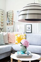 Pendant lamp with metal lampshade above side table and sofa with retro scatter cushions