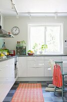 Simple, white fitted kitchen with orange rug on chequered floor