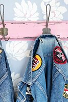 Denim jacket with fabric badges hanging on pink coat rack on pastel blue, floral wallpaper
