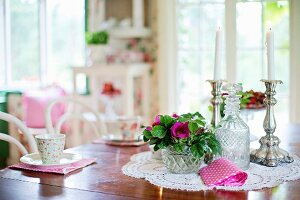 Bowl of flowers, crystal carafe and candlesticks on lace doily on dining table