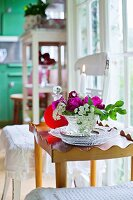 Bowl of flowers and lit candle on tray table