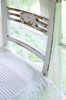 Kitchen chair with white, peeling paints and white lace seat cushion