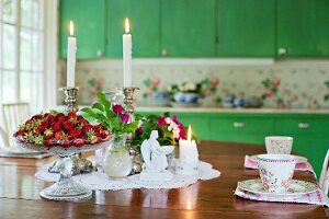 Table set with fresh strawberries, flowers and lit candles
