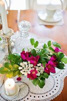 Bouquet of garden flowers and candles on lace doily