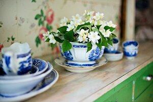 Bowl of jasmine amongst blue and white china crockery