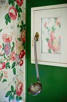 White cabinet with ladle hanging from handle mounted on green wall
