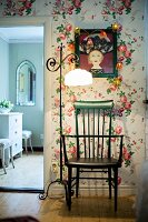 Green wooden chair and vintage standard lamp with pale lampshade against floral wallpaper next to open doorway