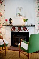 50s armchairs with green upholstery in front of open fireplace below crucifix in small niche