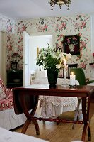 White bouquet in vase on antique wooden table in rustic interior with floral wallpaper