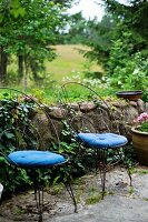 Delicate metal chairs with curved backrests and blue seat cushions in front of low, stone garden wall