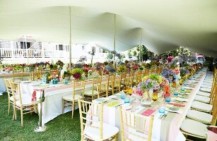 Long dining tables in garden set for birthday party