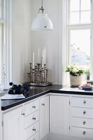 Silver candlesticks on L-shaped kitchen base units below retro pendant lamp
