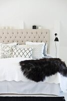 Scatter cushions and fur blanket on double bed with ecru, button-tufted headboard