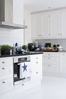 White, Scandinavian-style kitchen with black worksurface; tea towel with star motif