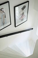 Framed, artistic photos above black handrail of winding staircase