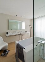 Free-standing white bathtub behind glass screen opposite twin washstands below large mirror in minimalist designer bathroom
