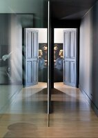 Glass partition in corridor leading to open door with view of artwork; traditional atmosphere in a modern setting