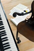 Piano keyboard, vintage armchair and sheet music lying on floor