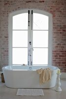 Bathmat in front of free-standing bathtub, white candle in large candlestick on floor and frosted French windows