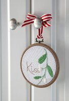 'Kiss' and mistletoe embroidered on fabric in embroidery hoop frame hung from door knob