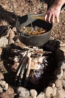Vegetable stew in cooking pot suspended over campfire
