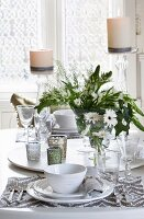 Place setting with white plates and patterned place mat; tealight holders and vases of flowers on lazy Susan