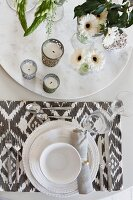 Place setting with white crockery and patterned table mat next to tealight holders and vases of flowers on round dish