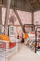 White, metal, throne-style chair with orange cushions, black metal bed and half-timbered walls with wallpaper panels