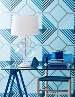 Blue geometric wallpaper, lamp on glass desk