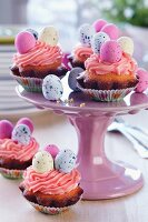 Easter cakes with topped with pink buttercream and sugar eggs on cake stand