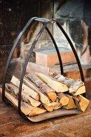 Firewood in curved metal rack in rustic fireplace