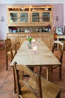 Solid wood dining table and chairs in front of dresser with fairy lights against pink-painted wall