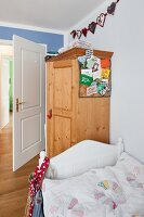 Bed with white wooden frame in front of farmhouse wardrobe in child's bedroom
