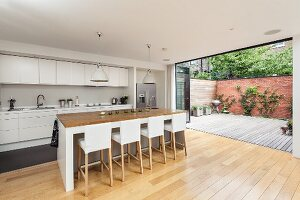 Bar stools with white loose covers in open-plan designer kitchen with open folding terrace doors to one side