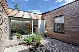 Planters on pebble area and wooden deck in courtyard of contemporary house with wood-clad facade