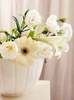 White flowers (lisianthus, gerbera daisies, lilies) in ceramic pot
