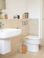 Sink and toilet on projecting wall with sand-coloured tiles in modern bathroom