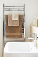 View across sink to stainless steel towel rack with towels of various sizes in shades of brown