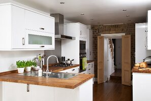 Modern, white fitted kitchens with wooden work surfaces; open double doors in brick wall in background