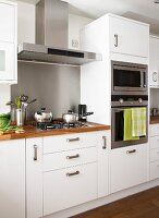 Gas hob with extractor hood and separate oven and microwave in white, fitted kitchen with wooden work surfaces