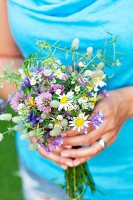 Woman holding posy of wild flowers
