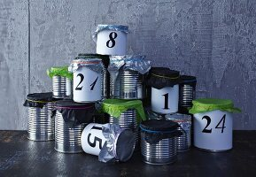 Hand-crafted Advent calendar made from tin cans with tissue paper lids