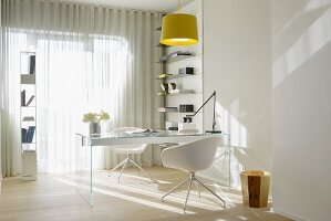 Glass desk, white designer chairs and airy storage shelves in office flooded with sunlight