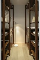 Walk-in wardrobe with dark brown shelves, white cotton storage elements and small standard lamp providing light
