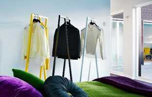Shirts and jumpers on designer clothes racks behind partially visible bed with scatter cushions of various colours and green bedspread