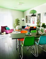 Colourful plastic chairs at black table below spherical pendant lamp; lounge area with sofa and beanbag below green-painted ceiling in modern interior